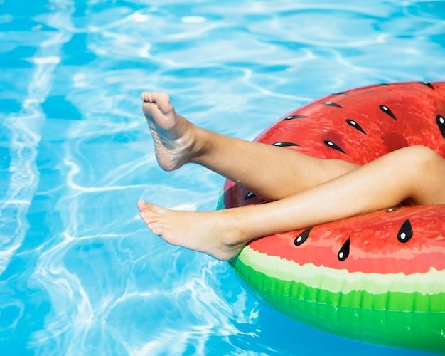 Mädchenbeine auf floatie im swimmingpool Kostenlose Fotos
