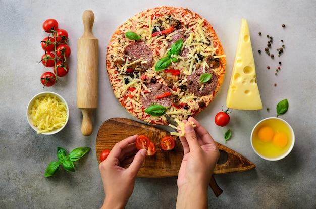 Mädchenhände, die pizza mit basilikum vorbereiten, verlässt auf hellgrauem hintergrund. Premium Fotos