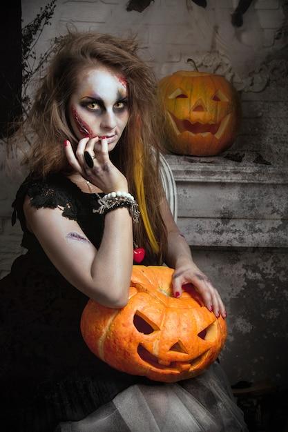 Mädchenhexenzombie isst den vogel vor halloween Premium Fotos