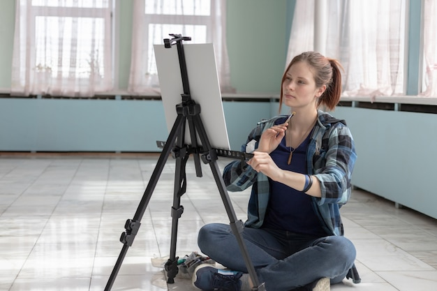Mädchenkünstler malt mit den ölfarben, die auf dem marmorboden sitzen. weiße leinwand und staffelei stehen auf dem boden von marmorfliesen im raum mit türkisfarbenen und hellgrünen wänden. Premium Fotos