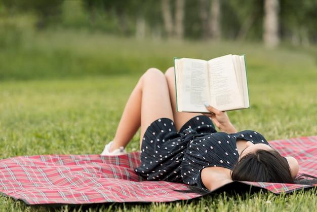 Mädchenlesung auf einer picknickdecke Kostenlose Fotos