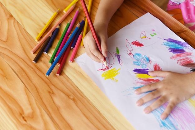 Mädchenmalerei auf papierblatt mit farbbleistiften auf dem holztisch zu hause - kinderkind, das zeichnungsbild und bunten zeichenstift tut Premium Fotos