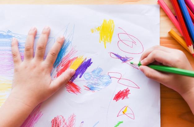 Mädchenmalerei auf papierblatt mit farbbleistiften auf dem kind des holztischs zu hause, das zeichnungsbild und bunten zeichenstift tut Premium Fotos