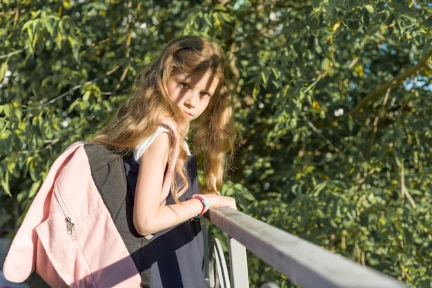 Mädchenschulmädchenblondine mit rucksack in der schuluniform nahe zaun im schulhof Premium Fotos