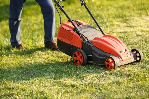 Mähtrimmer - arbeitskraftausschnittgras im grünen yard bei sonnenuntergang. mann mit elektrischem rasenmäher, rasenmähen. gärtner, der einen garten trimmt. Premium Fotos