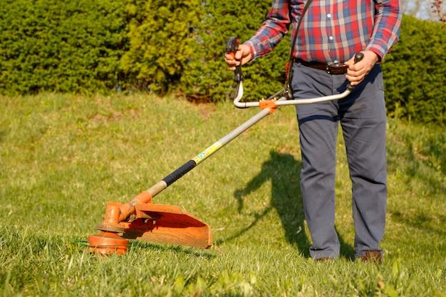 Mähtrimmer - arbeitskraftausschnittgras im grünen yard bei sonnenuntergang. Premium Fotos