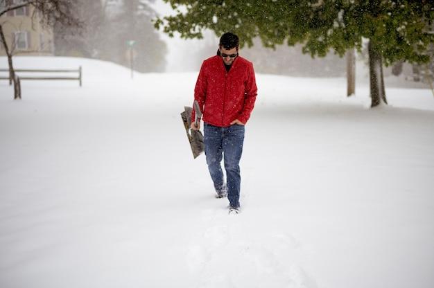 Männchen, das auf einem schneebedeckten feld geht, während die schneeschaufel hält Kostenlose Fotos