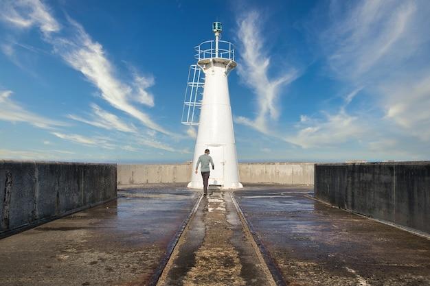 Männchen, das in richtung des leuchtturms in ost-london, südafrika geht. Kostenlose Fotos