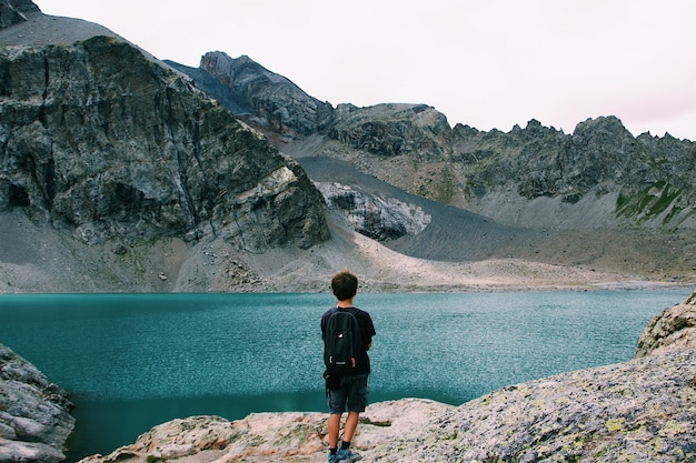 Männchen mit einem rucksack, der auf einer klippe steht und den blick auf das meer nahe einem berg genießt Kostenlose Fotos