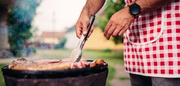 Männer, die das schutzblech grillt hühnerfleisch tragen Premium Fotos