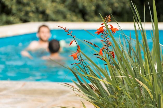 Männer, die im swimmingpool im yard stillstehen Kostenlose Fotos