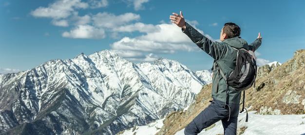 Männer feiern erfolg, indem sie ihre arme in den schneebedeckten bergen ausbreiten. erreichung ihrer ziele Premium Fotos