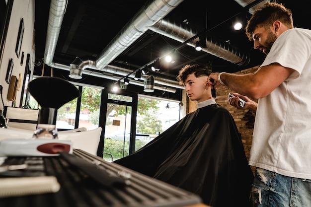 Männer-friseursalon. friseur, der haarschnitt im friseursalon tut. Premium Fotos