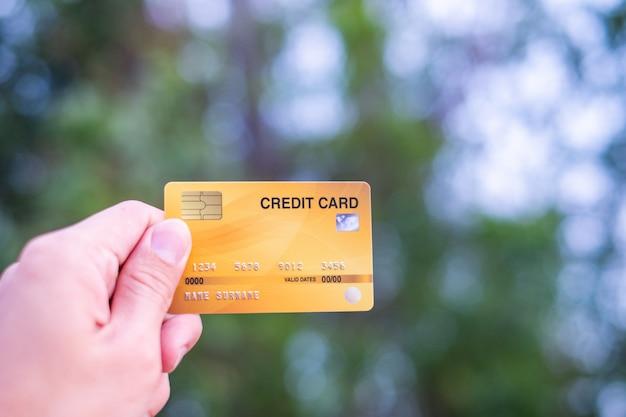 Männer halten kreditkarte auf bokeh natur Premium Fotos