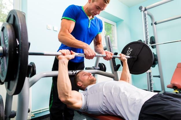 Männer im sportgymnastiktraining mit barbell für eignung Premium Fotos