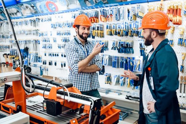 Männer in schutzhelmen wählen sie werkzeuge. Premium Fotos