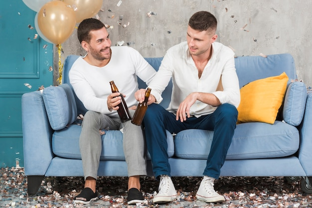 Männer mit bier auf blauer couch Kostenlose Fotos