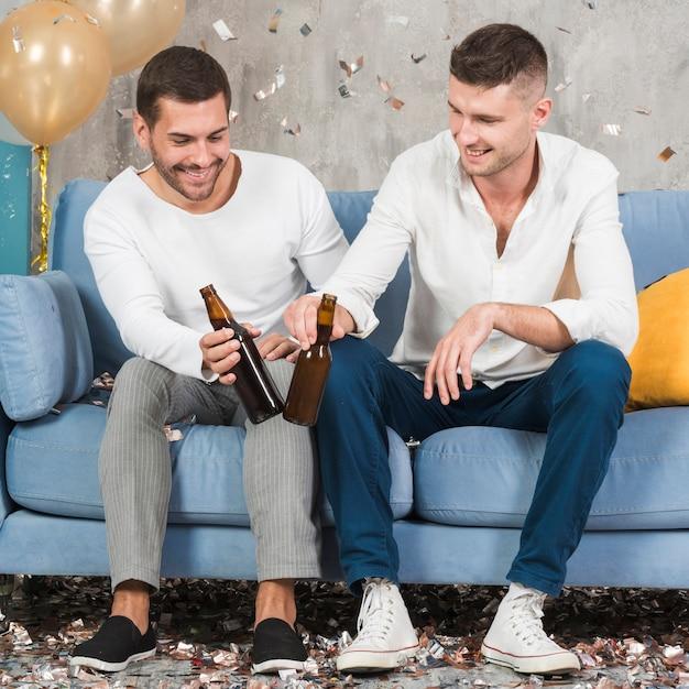 Männer mit bier auf der couch Kostenlose Fotos