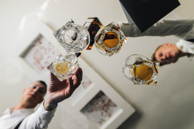 Männer nehmen gläser mit whisky von einem glastisch Kostenlose Fotos