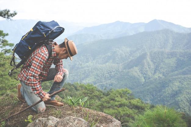 Männer sitzen und beobachten berge in tropischen wäldern mit rucksäcken im wald. abenteuer, reisen, klettern. Kostenlose Fotos