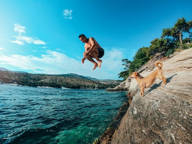 Männer springen vom felsigen ufer ins meer Premium Fotos