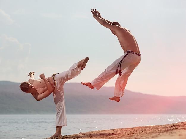 Männer trainieren capoeira am strand Premium Fotos