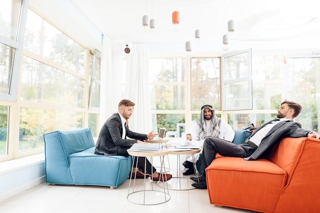 Männer und eine frau arbeiten in einem hellen büro. Premium Fotos