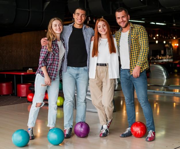 Männer und frauen, die in einem bowlingspielverein aufwerfen Kostenlose Fotos