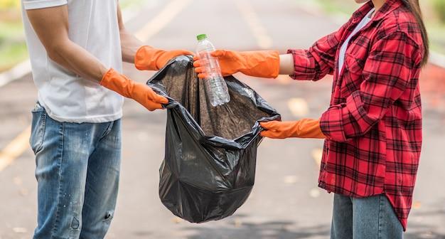 Männer und frauen helfen sich gegenseitig beim sammeln von müll. Kostenlose Fotos