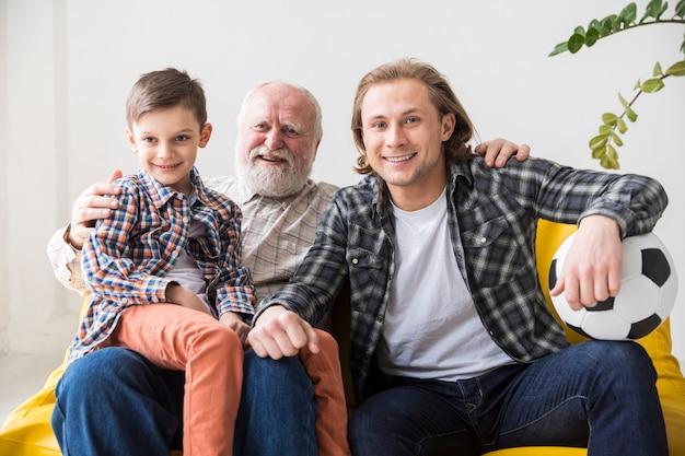 Männer unterschiedlicher generation, die auf der couch fernsehen Kostenlose Fotos
