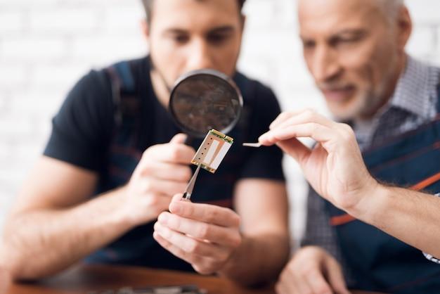 Männer untersuchen pc-komponente mit lupe. Premium Fotos