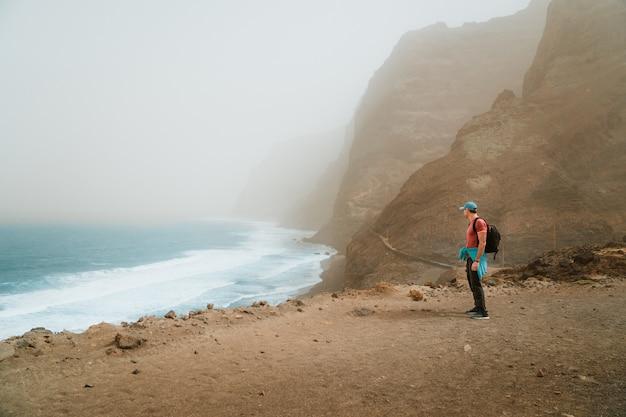 Männer wanderer mit rucksack auf der malerischen küstenstraße. die route führt entlang riesiger vulkangesteinklippen über dem tosenden ozean und verbindet die städte cruzinha und ponta do sol. santo antao. kap verde. Premium Fotos