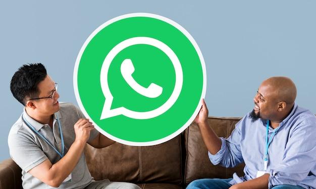 Männer zeigen ein whatsapp messenger-symbol Kostenlose Fotos