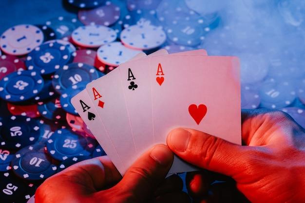 Männerhände halten askarten vor dem hintergrund des spielens von chips. das foto zeigt rauch Premium Fotos