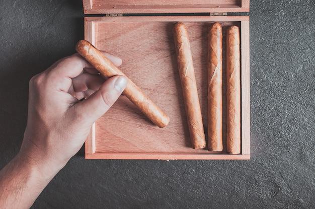 Männerhände nehmen eine zigarre aus der schachtel auf einem dunklen tisch Premium Fotos