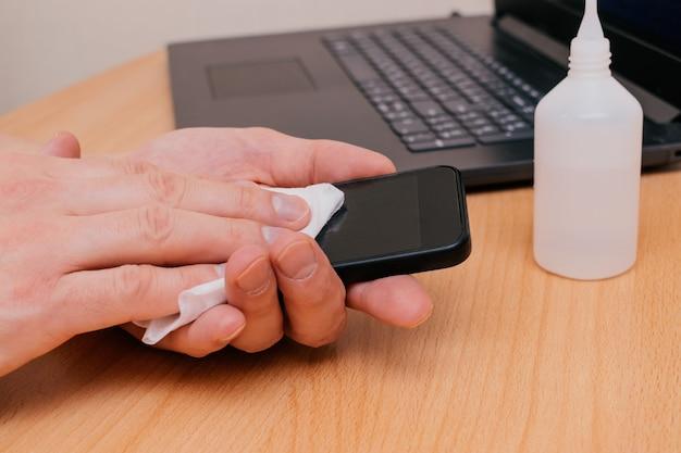 Männerhände reinigen das telefon mit einem antiseptischen feuchttuch. vorbeugung gegen coronavirus nach dem besuch öffentlicher plätze Premium Fotos