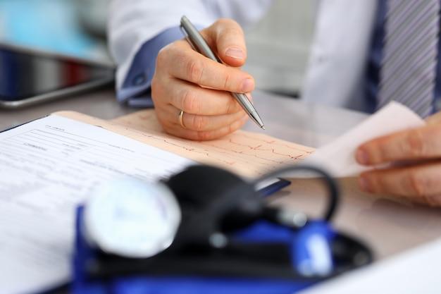 Männliche arzthände mit kardiogrammkarte Premium Fotos