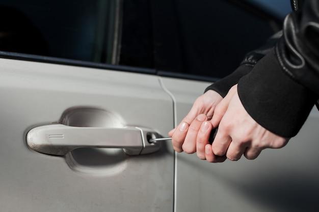 Männliche diebeshände, die versuchen, autotür mit schraubendreher zu öffnen. carjacker fahrzeug entsperren. carjacking gefahr Premium Fotos