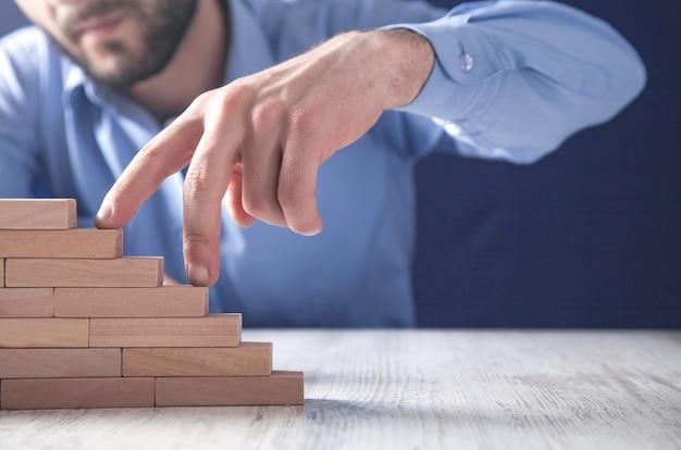 Männliche finger, die treppen auf holzklötzen steigen. Premium Fotos