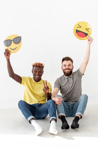 Männliche freunde des kopieraums, die auf boden sitzen und emoji halten Kostenlose Fotos