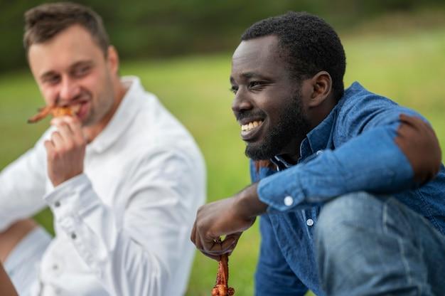Männliche freunde, die draußen grill essen Kostenlose Fotos