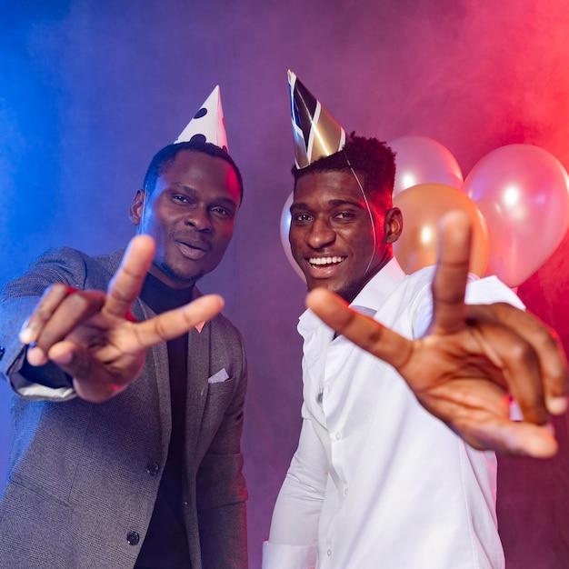 Männliche freunde, die friedenssymbol auf der party zeigen Premium Fotos