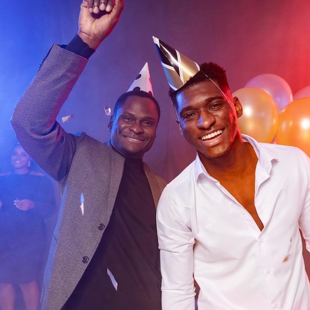Männliche freunde tragen partyhüte Premium Fotos
