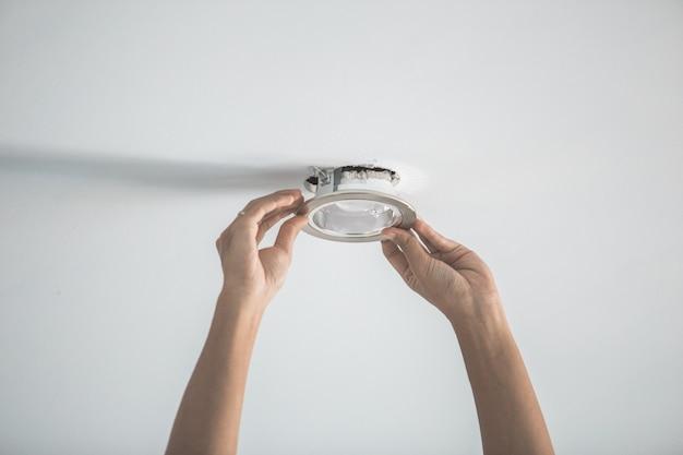Männliche hände, die die fassung für die glühbirne installieren Premium Fotos