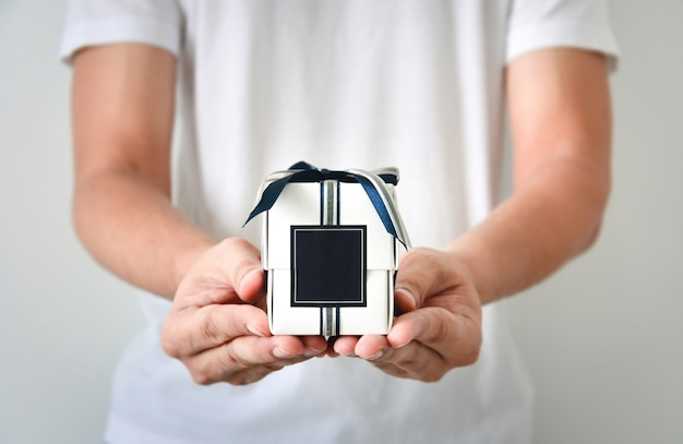Männliche hände, die eine kleine weiße geschenkbox eingewickelt mit blauem und silbernem farbband und dunkelblauem leerem aufkleber halten Premium Fotos