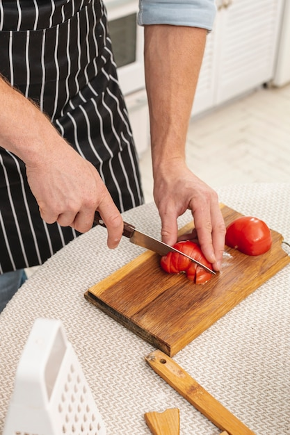 Männliche hände, die eine köstliche tomate schneiden Kostenlose Fotos