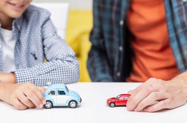 Männliche hände, die mit spielzeugautos spielen Kostenlose Fotos