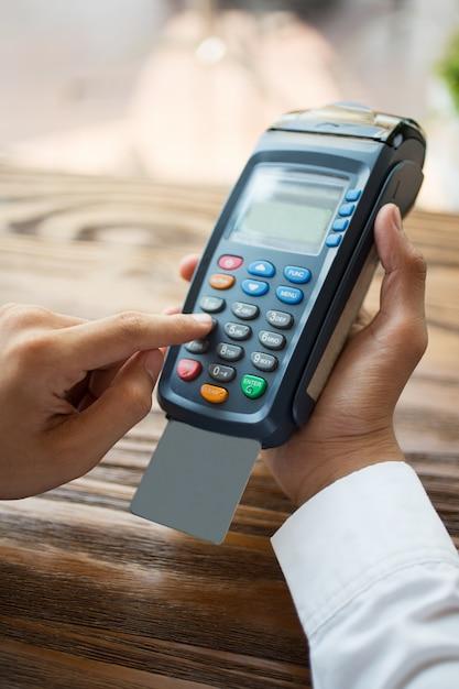 Männliche hände drückt knöpfe auf kreditkartenleser Premium Fotos