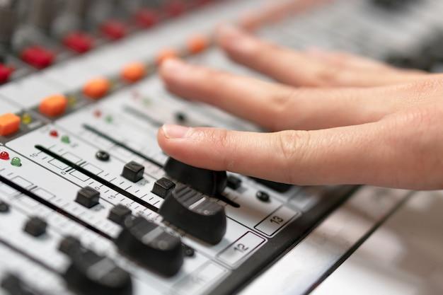 Männliche hand auf steuerfader auf konsole. mischpult eines tonstudios mit einem ingenieur oder musikproduzenten. Premium Fotos