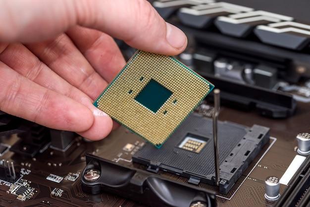 Männliche hand, die cpu-chip vom motherboard abnimmt Premium Fotos